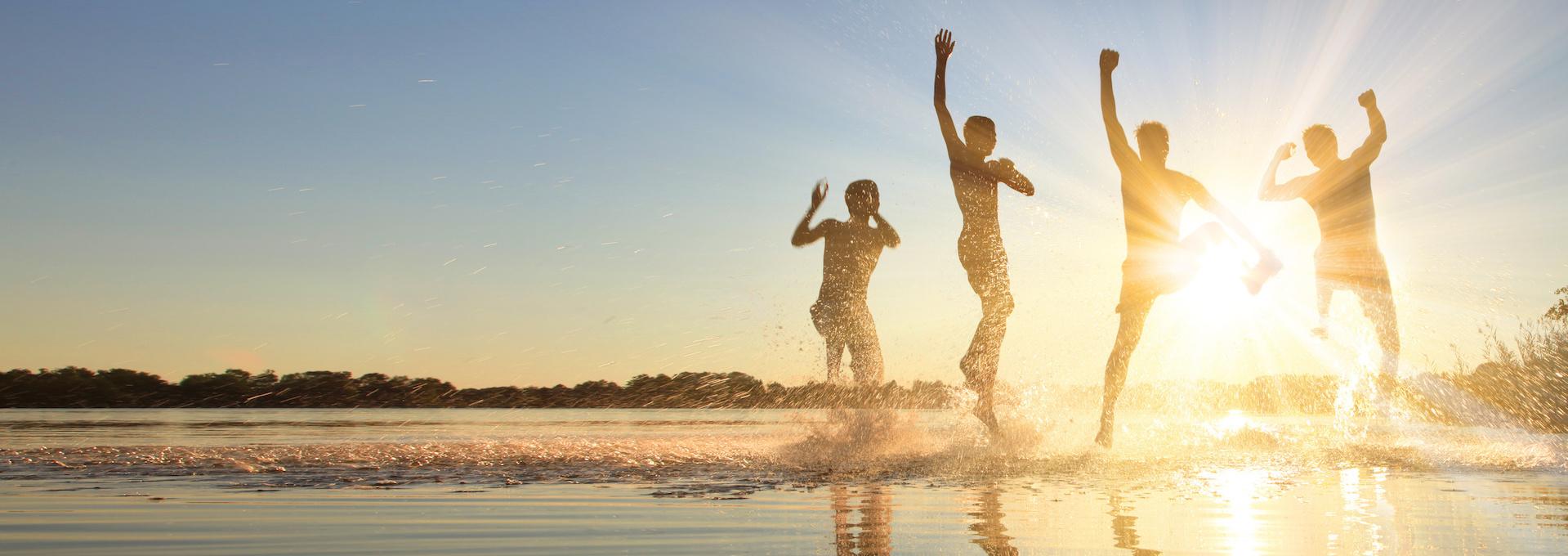 Glückliche junge Menschen laufen und springen am See beim Sonnenuntergang